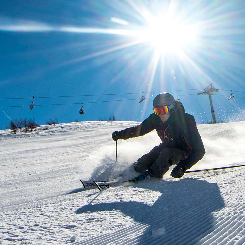 Bruce Crowley, private ski instructor skiing with sun behind him