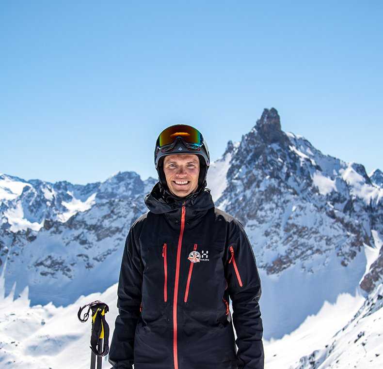 Ski instructor standing in snow with mountain behind