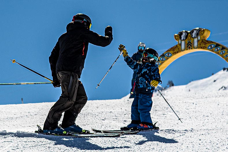 Child high fives his ski instructor on the ski slopes