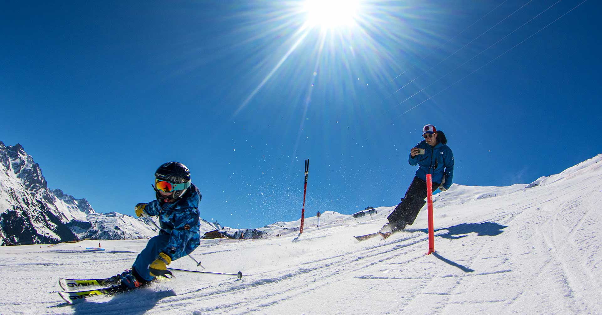Child skiing with instructor filming behind